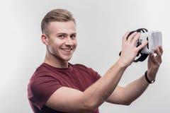 hombre Rubio-cabelludo que siente excitado sosteniendo los vidrios de la realidad virtual foto de archivo