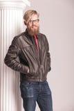 Hombre rubio de la barba que presenta cerca de una columna blanca Imagenes de archivo