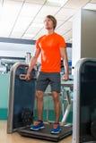Hombre rubio de la máquina del gimnasio del entrenamiento agazapado del ejercicio Imágenes de archivo libres de regalías