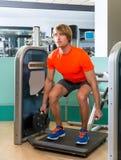 Hombre rubio de la máquina del gimnasio del entrenamiento agazapado del ejercicio Fotos de archivo