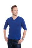 Hombre rubio joven aislado en el jersey azul que mira de lado al te Imágenes de archivo libres de regalías