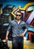 Hombre rubio joven atractivo contra la pared colorida de la pintada Foto de archivo
