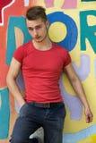 Hombre rubio joven atractivo contra la pared colorida de la pintada Fotografía de archivo