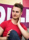 Hombre rubio joven atractivo contra la pared colorida de la pintada Imagen de archivo libre de regalías
