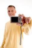 Hombre rubio que muestra las cámaras digitales Imagen de archivo libre de regalías