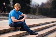 Hombre rubio que se sienta al aire libre Foto de archivo