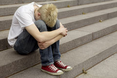 Hombre rubio que se sienta en las escaleras Imagen de archivo libre de regalías