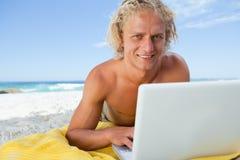 Hombre rubio sonriente que miente en la playa mientras que usa su ordenador portátil Imagen de archivo libre de regalías