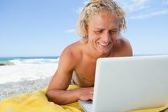 Hombre rubio sonriente que mira su computadora portátil Foto de archivo