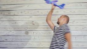 hombre 30-s que juega con el aeroplano del juguete Escena divertida metrajes