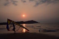 Hombre sailboarding en la puesta del sol Foto de archivo libre de regalías