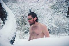 Hombre salvaje desnudo en gafas de sol el bosque nevoso del invierno Foto de archivo