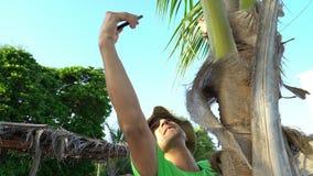 Hombre salvaje que sube en árbol y que intenta hacer una conexión en su teléfono celular Falta del naufragio del accidente de civ almacen de metraje de vídeo