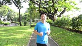 Hombre sano de la forma de vida en la ropa de deportes que funciona con y que mira su reloj en el parque en la puesta del sol