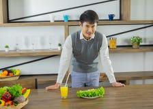 Hombre sano joven asiático, soporte en la mesa de comedor en la cocina imagen de archivo libre de regalías
