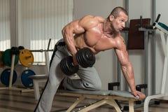 Hombre sano que hace el ejercicio pesado para la parte posterior Fotografía de archivo