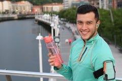 Hombre sano que sostiene la botella de agua después de un funcionamiento en las calles de la ciudad Fotos de archivo libres de regalías