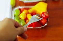 Hombre sano que usa una bifurcación para comer en la oficina una ensalada de fruta fresca deliciosa en la caja de aluminio en la  imagenes de archivo