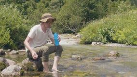 Hombre sediento que toma la botella de agua de la corriente de la montaña y que bebe en acampar almacen de video