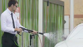 Hombre seguro de sí mismo que lava el auto costoso con agua, tomando el cuidado del coche de la élite metrajes