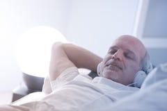 Hombre seguro de sí mismo que se relaja en un sofá imagen de archivo libre de regalías
