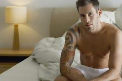 Hombre semi desnudo que se sienta en cama Foto de archivo libre de regalías
