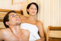 Hombre semidesnudo y muchacha que se relajan en sauna Foto de archivo