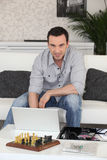 Hombre sentado con la computadora portátil fotografía de archivo