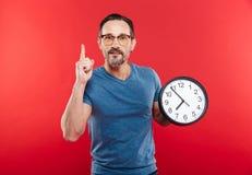 Hombre serio adulto que sostiene el reloj Imagen de archivo libre de regalías