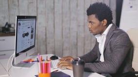 Hombre serio afroamericano que trabaja en la oficina almacen de video