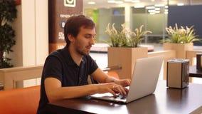 Hombre serio con el ordenador portátil en café almacen de metraje de vídeo