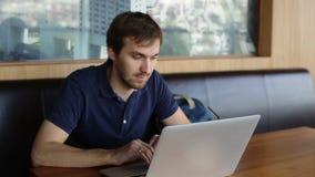 Hombre serio con el ordenador portátil en café almacen de video