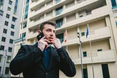 Hombre serio con un hombre de negocios de la barba que habla en el teléfono en el fondo del paisaje urbano Imágenes de archivo libres de regalías