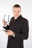Hombre serio con vidrios y un teléfono foto de archivo