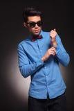 Hombre serio de la moda que fija su camisa Imagenes de archivo