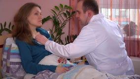 Hombre serio del doctor que examina a la mujer paciente joven con el estetoscopio en cama en casa almacen de metraje de vídeo