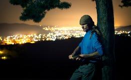 Hombre serio en el bosque en la noche con un cuchillo Foto de archivo