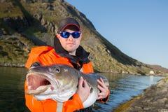 Hombre serio en el pescador de los vidrios que sostiene un bacalao del ogromnyu de los pescados Fotos de archivo