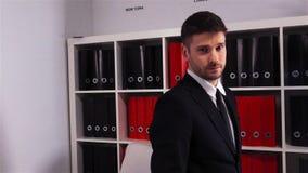 Hombre serio en mirada épica del traje formal en la cámara almacen de metraje de vídeo