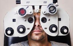 Hombre serio en phoropter con la calibración del ojo Fotos de archivo libres de regalías