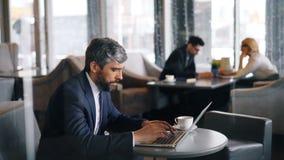 Hombre serio en traje formal usando el ordenador portátil que mecanografía en el café que se sienta en la tabla solamente metrajes