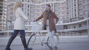 Hombre serio hermoso en capa marrón y los vaqueros azules claros que se colocan con su bicicleta en la ciudad delante del edifici almacen de metraje de vídeo