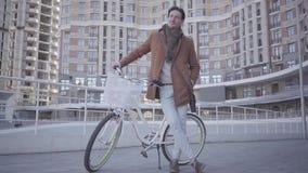 Hombre serio hermoso en capa marrón y los vaqueros azules claros que se colocan con su bicicleta en la ciudad delante del edifici metrajes