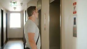 Hombre serio hermoso en la camiseta gris que espera un elevador Empujar un botón que llama una elevación almacen de metraje de vídeo