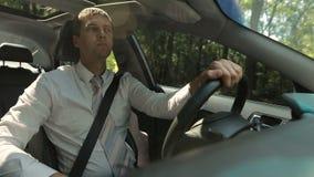 Hombre serio hermoso que conduce el coche en el camino rural almacen de metraje de vídeo
