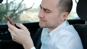 Hombre serio joven con una barba que se sienta en el coche y los controles el teléfono metrajes
