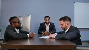 Hombre serio joven que sostiene los papeles, leyéndolos atento, durante la reunión en oficina metrajes