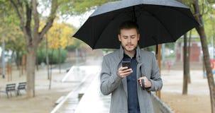 Hombre serio que comprueba el teléfono que camina debajo de la lluvia