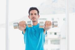 Hombre serio que ejercita con pesas de gimnasia en estudio de la aptitud Imágenes de archivo libres de regalías