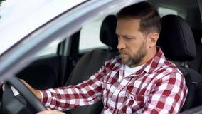 Hombre serio que se sienta en el coche, esperando en el tráfico el atasco, hora punta, anticipación imagen de archivo